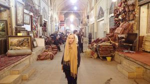 Ingrid Sørensen, dancer and painter, stands in the middle of market Bazaar in Isfahan, Iran wearing a yellow hijab loose around her face, and a blue sweater and dark jeans. Image is slightly washed out and dusty.